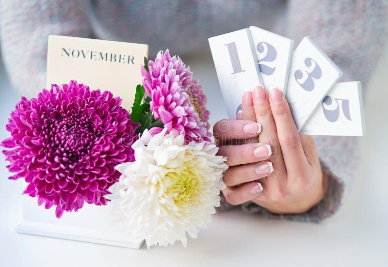 Mãos da mulher que guardam datas de calendário fotografia de stock