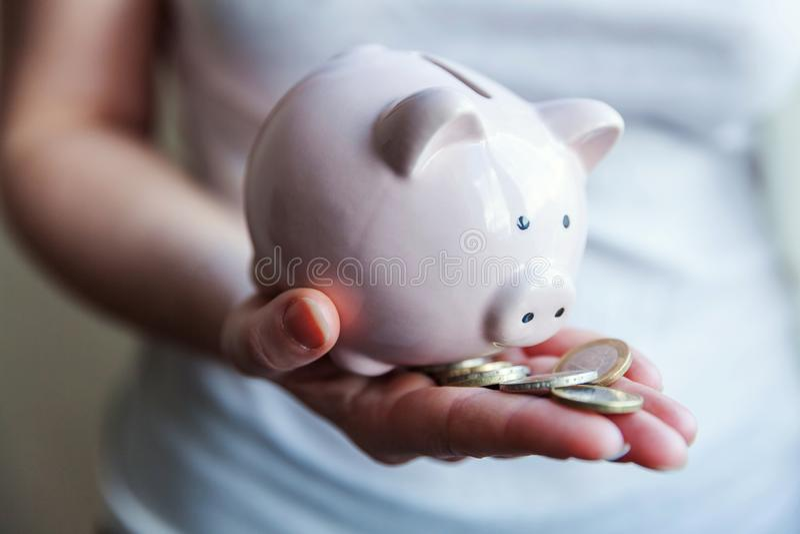 Mãos da mulher que guardam moedas cor-de-rosa do mealheiro e do euro fotografia de stock royalty free