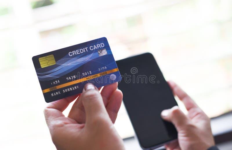 Mãos da mulher que guardam o cartão de crédito e que usam o smartphone para a compra em linha/povos que paga a carteira do dinhei imagens de stock