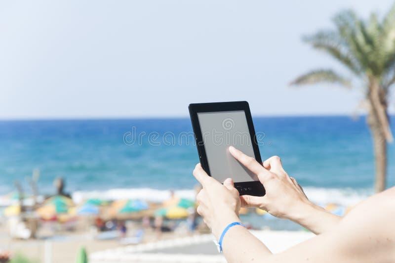 Mãos da mulher que guardam o leitor do ebook foto de stock