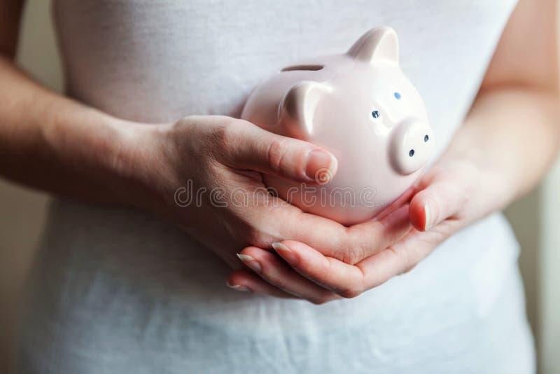 Mãos da mulher que guardam o mealheiro cor-de-rosa imagem de stock royalty free