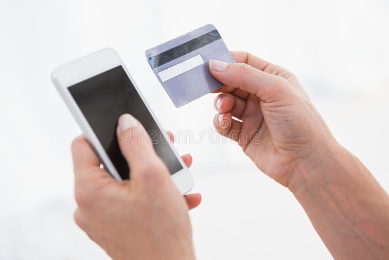 Mãos da mulher que guardam o smartphone e o cartão de crédito imagens de stock