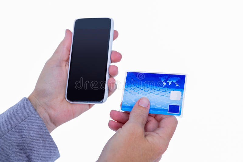 Mãos da mulher que guardam o smartphone e o cartão de crédito imagem de stock
