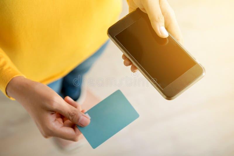 Mãos da mulher que guardam o smartphone e o cartão de crédito fotografia de stock