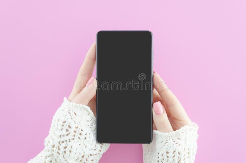 Mãos da mulher que guardam o telefone celular no fundo cor-de-rosa com espaço da cópia Configuração lisa Vista superior Zombaria  imagens de stock royalty free