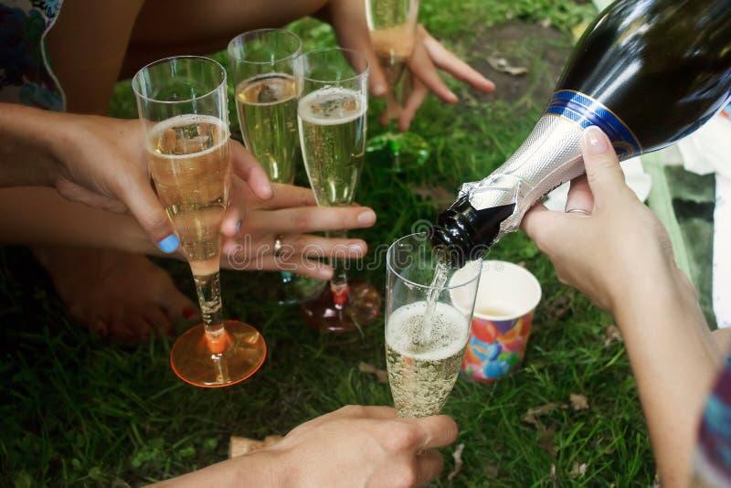 Mãos da mulher que guardam vidros coloridos e que derramam o champanhe em fotografia de stock