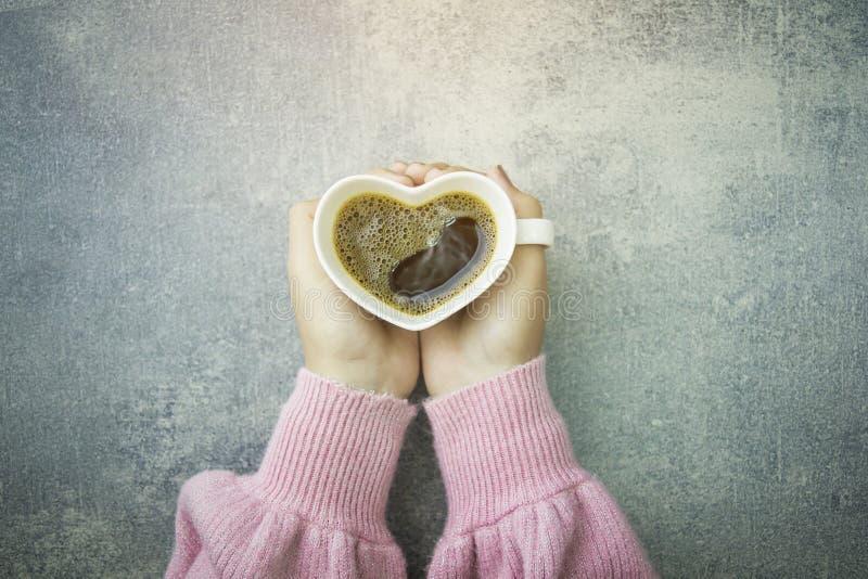 Mãos da mulher que guardam a xícara de café da forma do coração fotos de stock royalty free