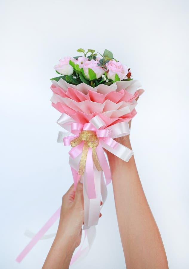 Mãos da mulher que mantêm o ramalhete cor-de-rosa artificial das rosas isolado no fundo branco fotografia de stock royalty free