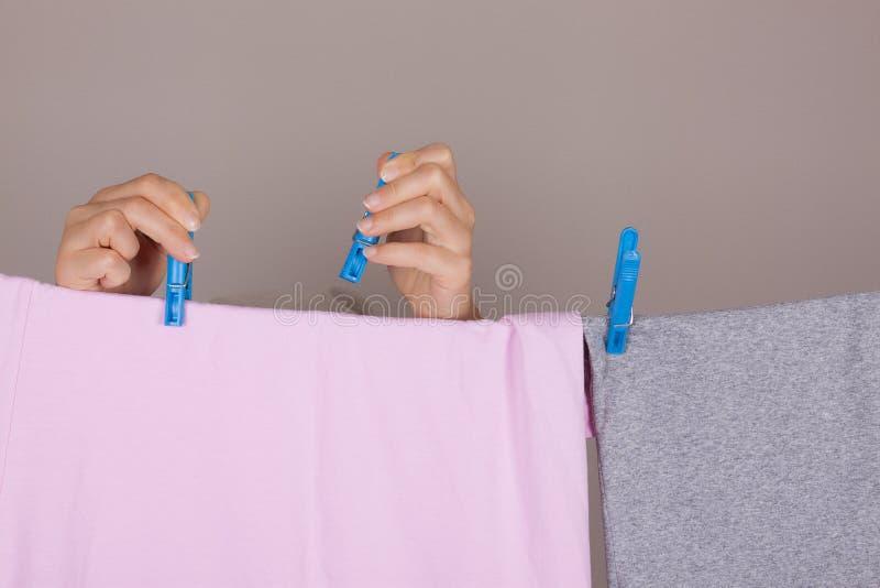 Mãos da mulher que penduram o pano limpo molhado para secar na linha de roupa no La foto de stock