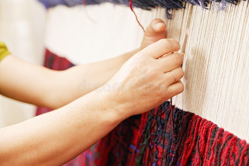 Mãos da mulher que tecem o tapete imagens de stock royalty free