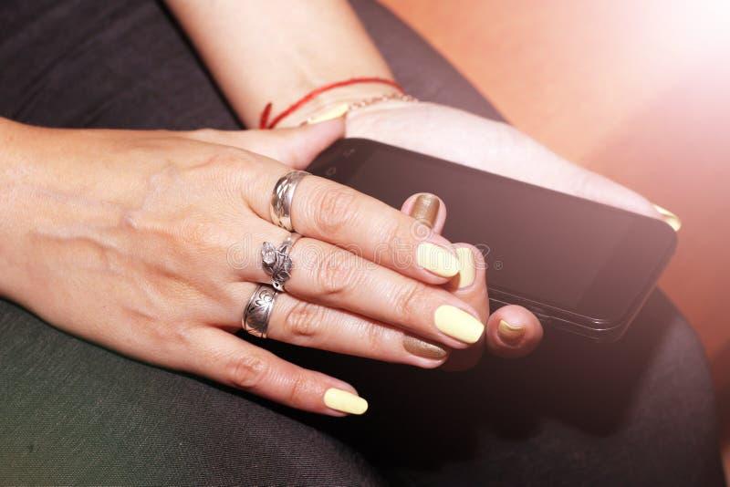 Mãos da mulher que tocam no fundo brilhante do smartphone imagem de stock