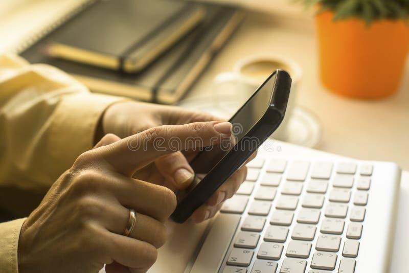 Mãos da mulher que tocam no smartphone e no teclado foto de stock royalty free