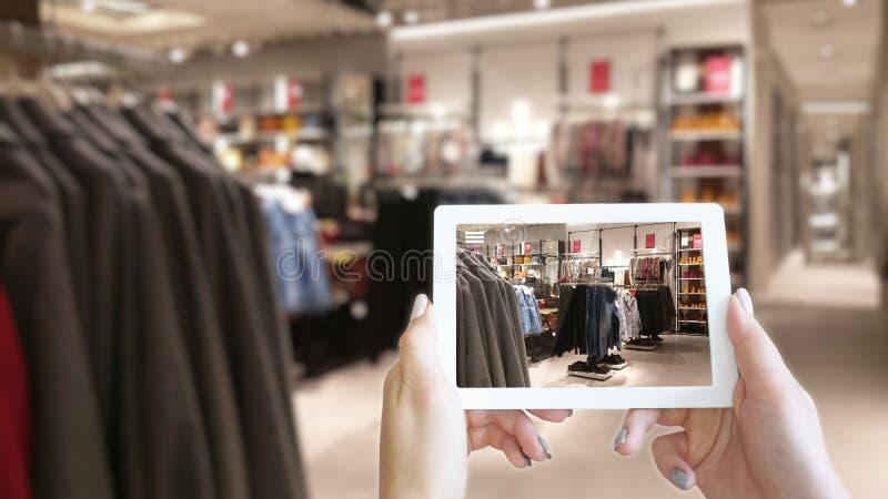Mãos da mulher que tomam uma tabuleta no shopping com imagem borrada da loja de roupa fotos de stock royalty free