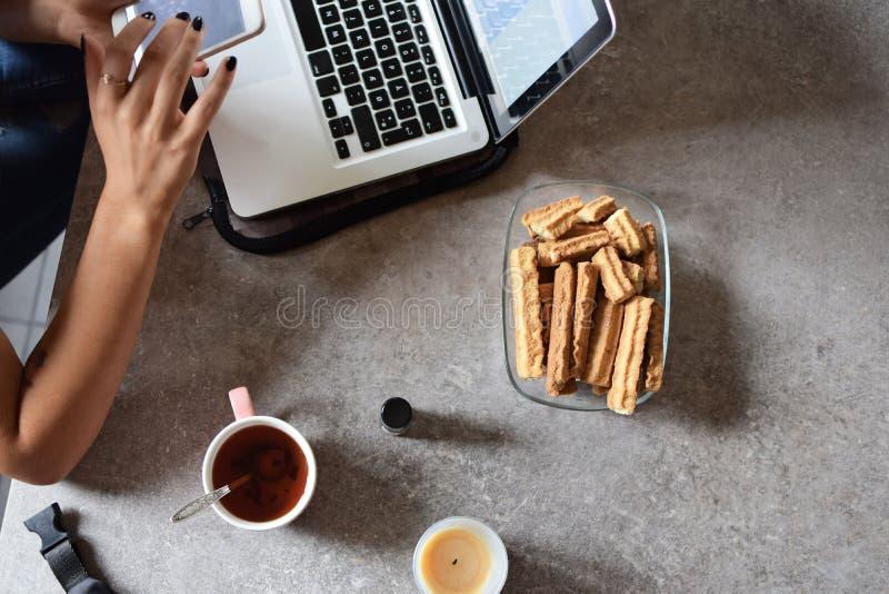 Mãos da mulher que trabalham com portátil e smartphone imagens de stock royalty free