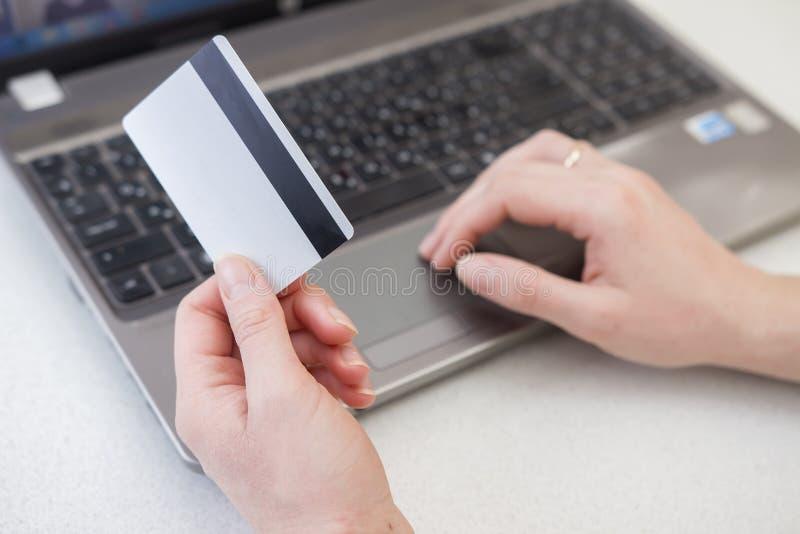 Mãos da mulher que usa o portátil e guardando o cartão de crédito plástico Conceito em linha dos pagamentos Compra em lojas do In foto de stock royalty free