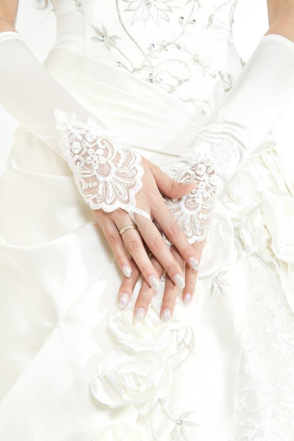 Mãos da noiva com manicure nas luvas brancas do laço fotografia de stock royalty free