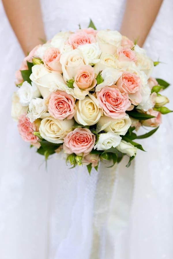 Mãos da noiva que guardam o ramalhete do casamento de rosas cor-de-rosa e brancas fotos de stock royalty free