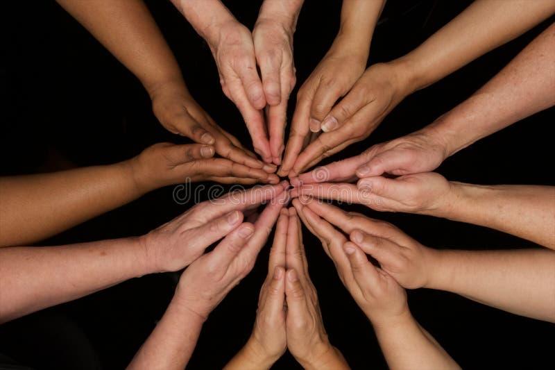 Mãos da oração das mulheres da diversidade que trabalham cooperativamente as mãos nos corações imagem de stock