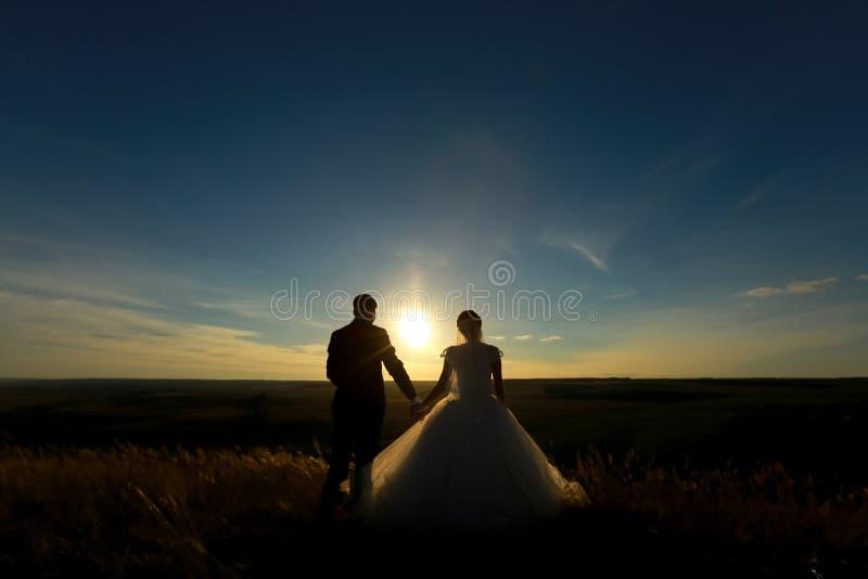 Mãos da posse dos pares do casamento no por do sol Silhueta dos noivos imagem de stock