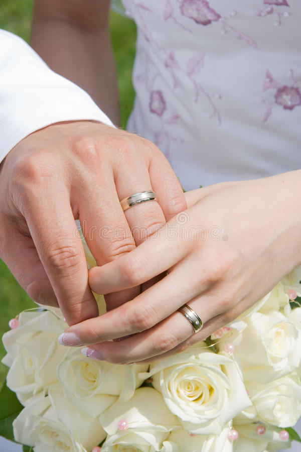 Mãos da terra arrendada com anéis de casamento imagem de stock royalty free