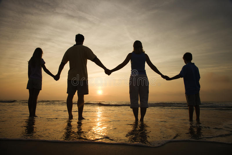 Mãos da terra arrendada da família na praia que presta atenção ao por do sol fotografia de stock royalty free