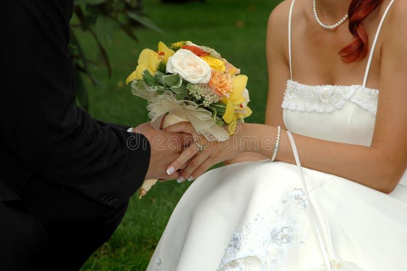 Mãos da terra arrendada da noiva e da vassoura foto de stock royalty free