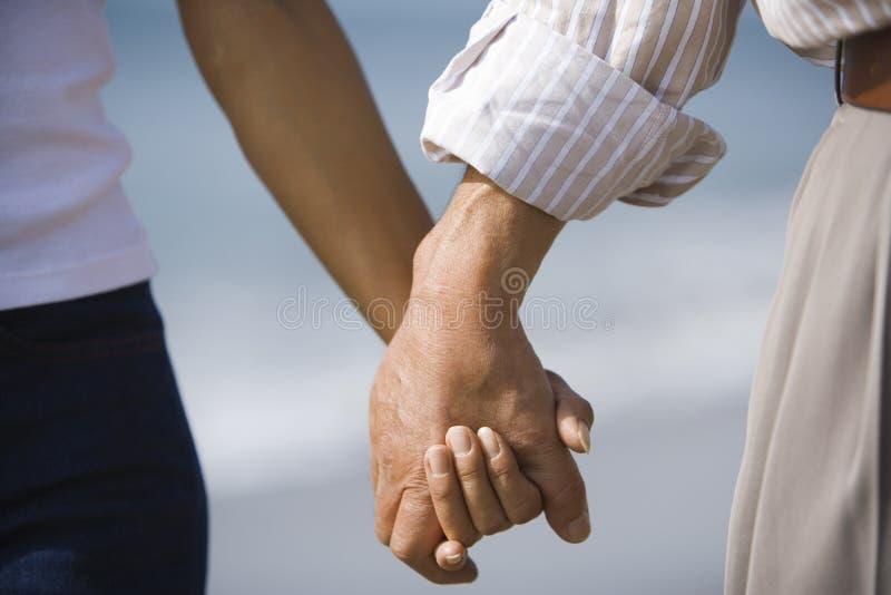 mãos da terra arrendada do marido e da esposa imagem de stock