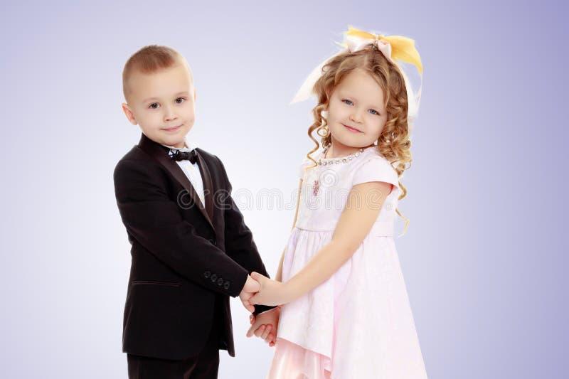 Mãos da terra arrendada do menino e da menina foto de stock royalty free