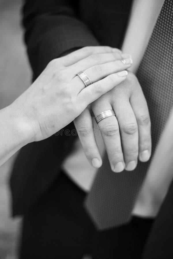 Mãos da terra arrendada do noivo e da noiva imagens de stock