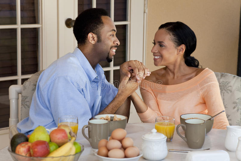 Mãos da terra arrendada dos pares do americano africano no pequeno almoço fotografia de stock royalty free