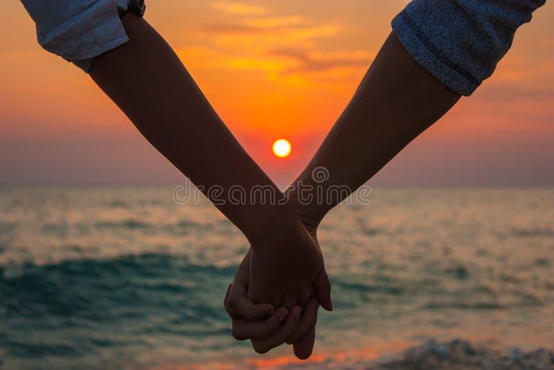 Mãos da terra arrendada dos pares no por do sol do mar imagem de stock