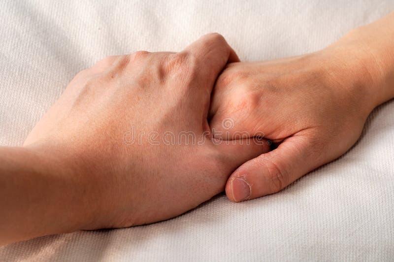 Mãos da terra arrendada na cama