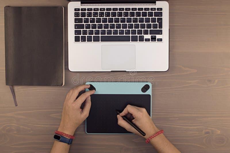mãos da vista superior na tabela, na tabuleta do desenho, no portátil e no telefone como fotos de stock