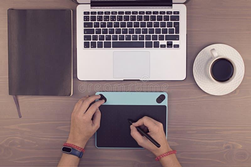mãos da vista superior na tabela, na tabuleta do desenho, no portátil e no telefone como fotografia de stock royalty free
