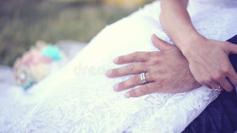 Mãos das alianças de casamento vestindo de uns noivos imagens de stock