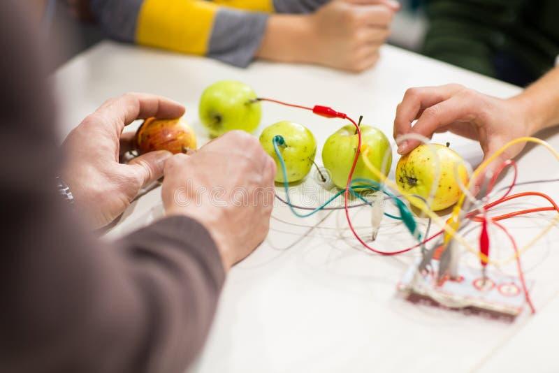 Mãos das crianças com o jogo da invenção na escola da robótica imagem de stock