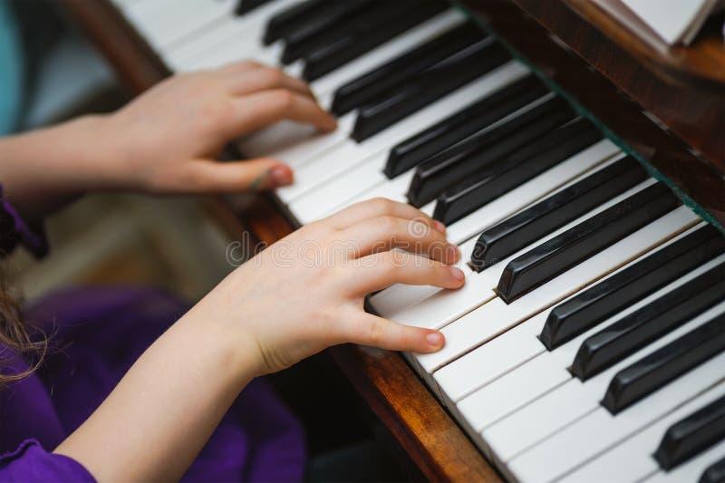 Mãos das crianças em uma chave branca do piano imagens de stock