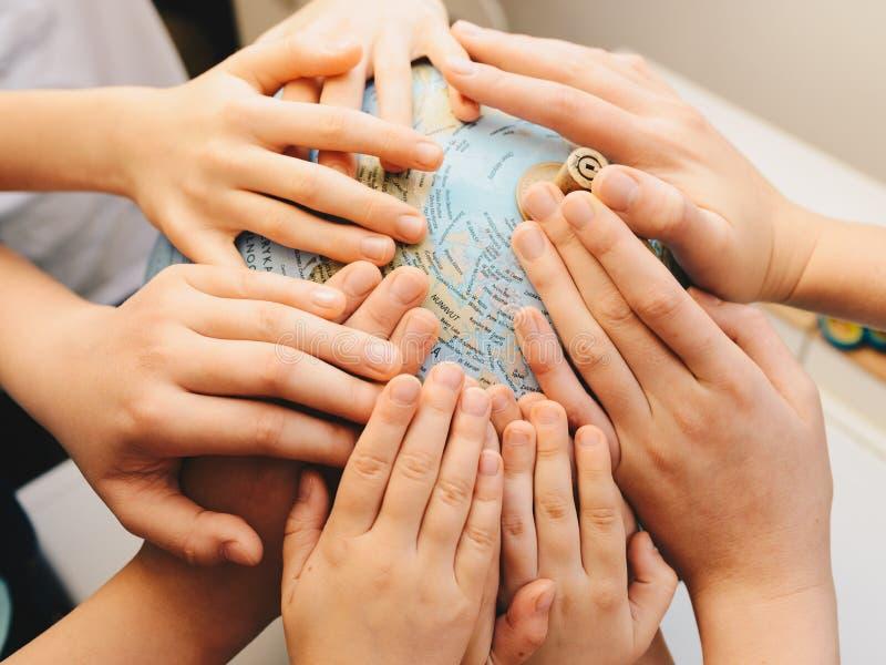 Mãos das crianças junto no globo - conceito da diversidade fotos de stock