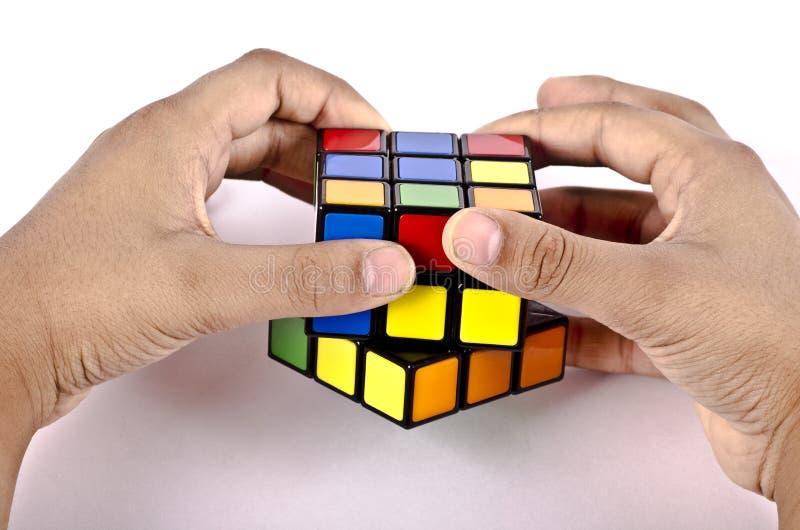 Mãos das crianças que resolvem o cubo do rubics fotografia de stock royalty free