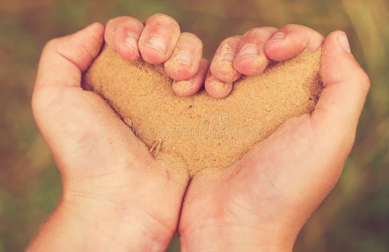 Mãos das crianças sob a forma do coração com areia fotos de stock
