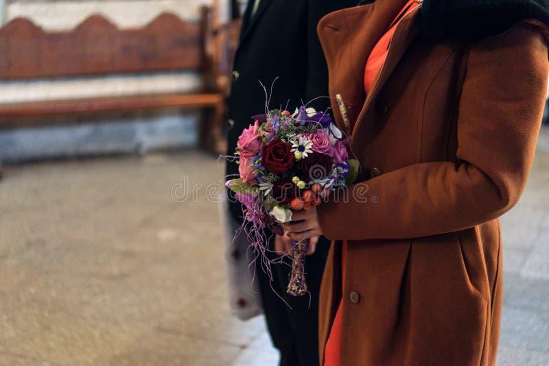 Mãos das damas de honra com close-up do ramalhete e do groomsman em trad fotos de stock
