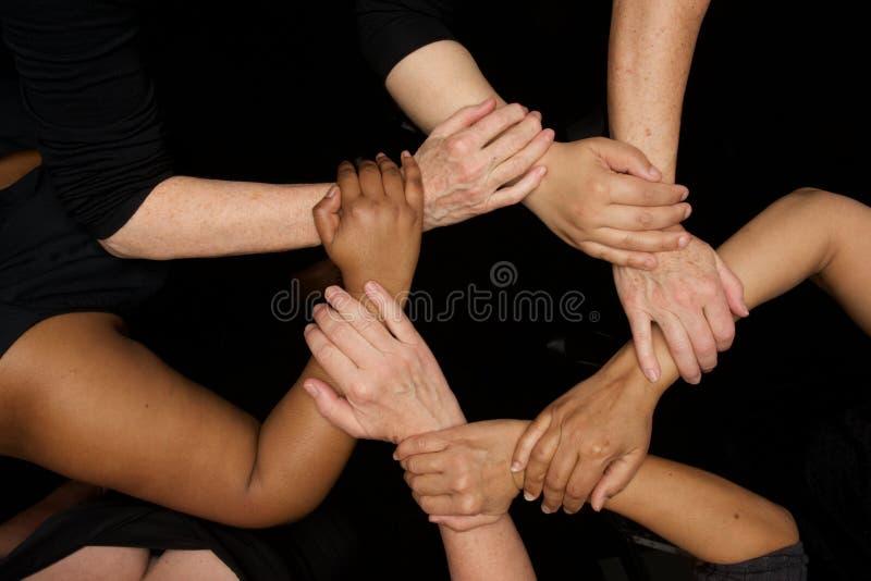 Mãos das mulheres da diversidade que trabalham cooperativamente as mãos nos corações foto de stock royalty free