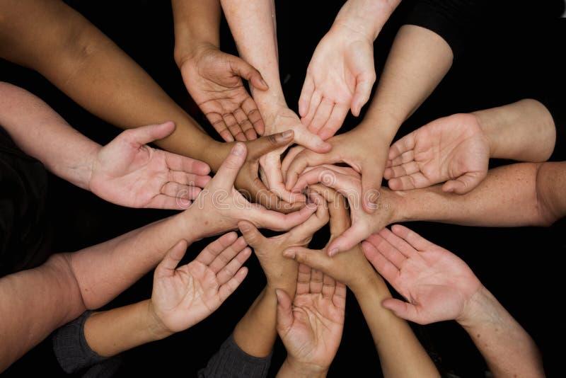 Mãos das mulheres da diversidade que trabalham cooperativamente as mãos nos corações imagens de stock royalty free