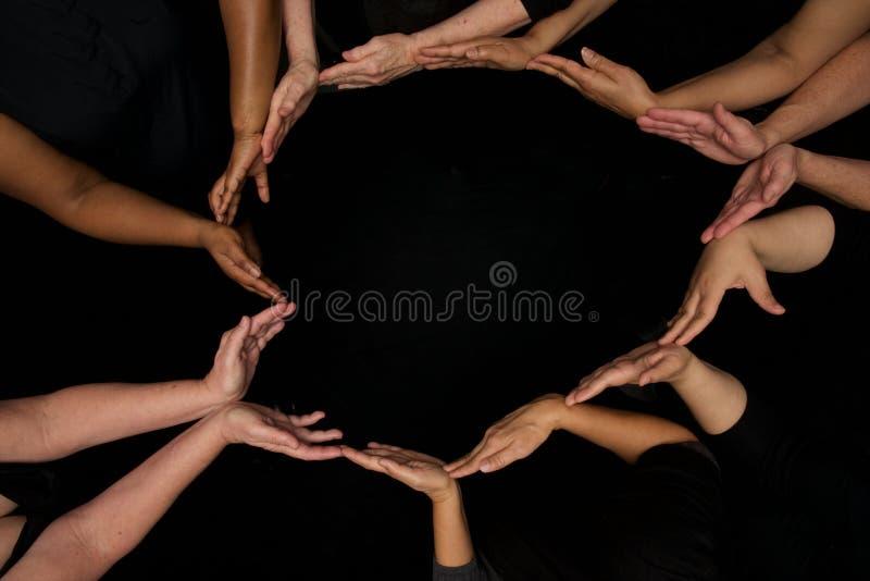 Mãos das mulheres da diversidade que trabalham cooperativamente as mãos nos corações imagens de stock