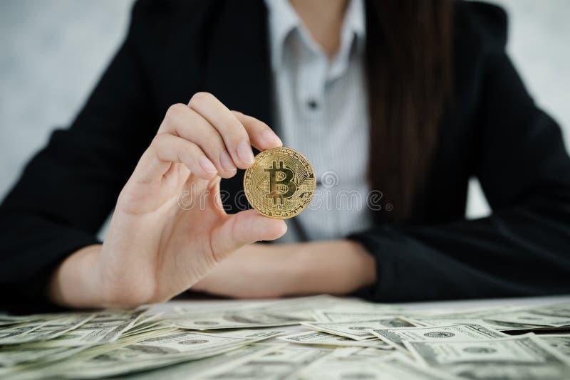 Mãos das mulheres de negócio que guardam Bitcoin e pilha do dólar do dinheiro sobre foto de stock royalty free