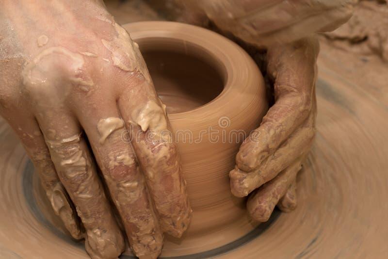 Mãos das mulheres em processo de fazer a bacia da argila na roda da cerâmica fotografia de stock royalty free