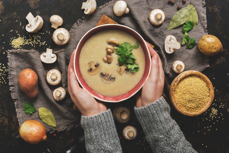Mãos das mulheres em uma camiseta cinzenta que guarda uma bacia de creme de cogumelo Sopa quente do inverno em um fundo rústico e fotografia de stock