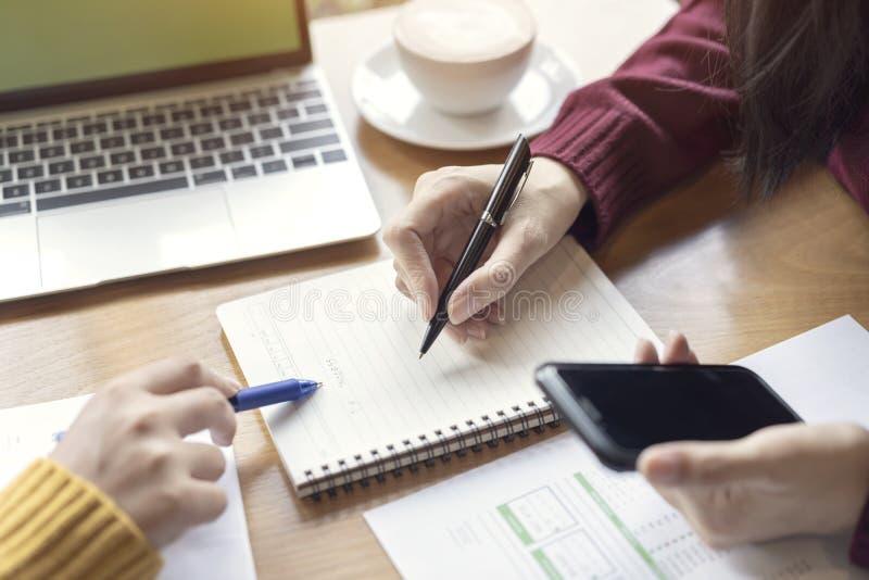 Mãos das mulheres que apontam a programação do planeamento do sucesso no livro de nota Equipe criativa nova do colega de trabalho fotos de stock royalty free