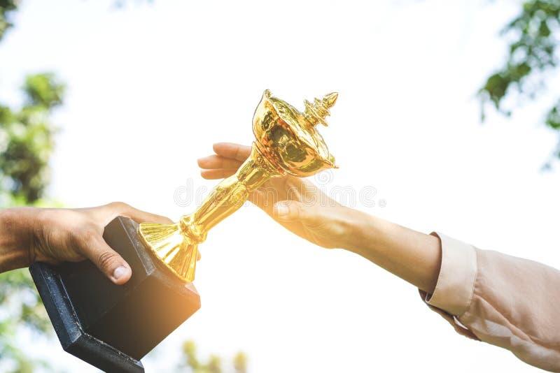 Mãos das mulheres que trabalham no escritório, recebendo troféus fotos de stock