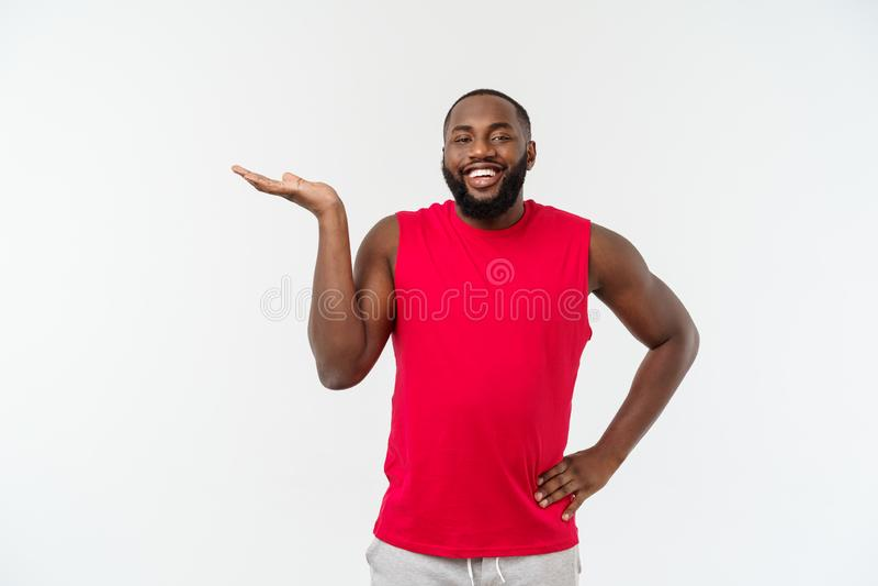 Mãos de alargamento do homem afro-americano novo do esporte ao lado para que convidar venha foto de stock